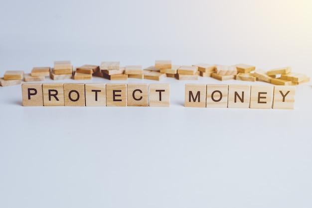 Le parole proteggi soldi fatte con lettere di legno a blocchi. legno abc