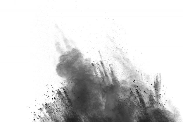 Le particelle nere schizzano su fondo bianco. polvere di polvere nera che esplode.