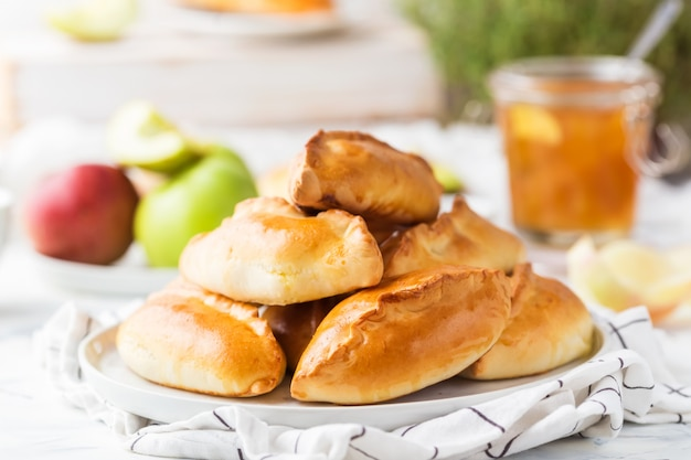 Le pasticcerie russe tradizionali hanno riempito di mele su una zolla bianca