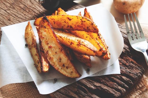 Le patate al forno sono servite sul bordo di legno rustico. cibo vegano o spuntino cibo salutare