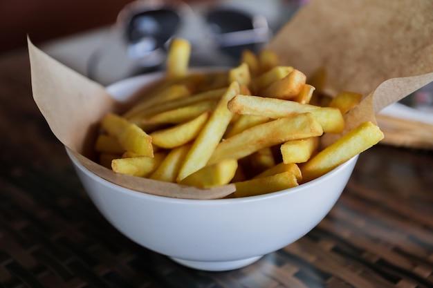 Le patate fritte in ciotola bianca sono servito con la carta del mestiere sulla tavola