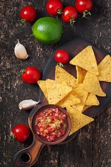 Le patatine fritte e la salsa messicane del nacho si tuffano in ciotola su di legno