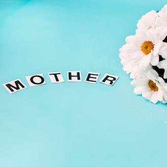 Le pedane dei fiori bianchi sulla madre blu di parola del fondo fiorisce per la madre