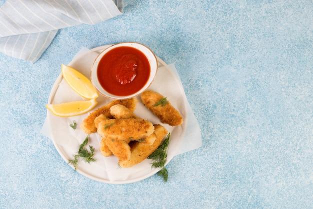 Le pepite di pollo fatte in casa su un piatto si trovano su uno sfondo concreto. vista dall'alto