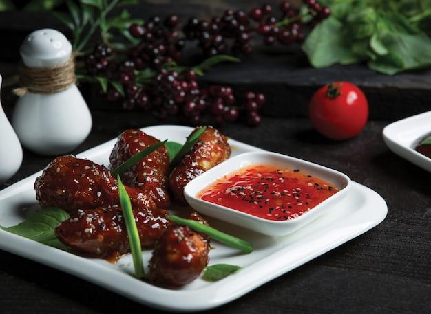 Le pepite di pollo in teriyaki sauca e il peperoncino piccante si immergono in un piatto bianco