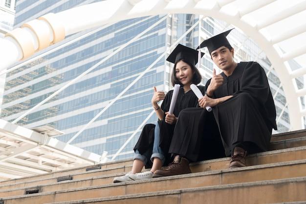 Le persone adolescenti laureate felici si siedono con gli abiti di laurea nella cerimonia di congratulazioni.