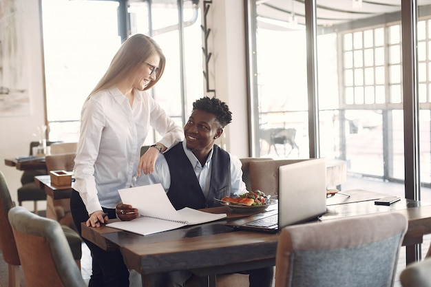 Le persone alla moda lavorano in un ufficio e usano il laptop