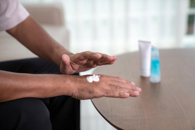 Le persone anziane che usano gel per alcool e crema idratante si puliscono le mani per prevenire un virus covid19