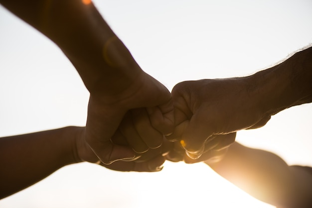 Le persone che danno un pugno mostrano unità e lavoro di squadra. amicizia, concetto di partnership.