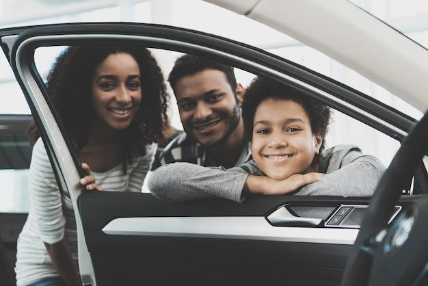 Le persone che guardano attraverso la finestra di automobile famiglia acquistare auto.