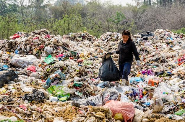 Le persone che lavorano nello smaltimento dei rifiuti municipali aprono il processo di discarica