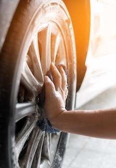 Le persone che puliscono e lavano la macchina