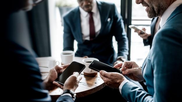 Le persone che usano i loro telefoni in una riunione