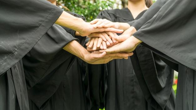 Le persone con abiti neri si uniscono a mano nel raggruppamento.