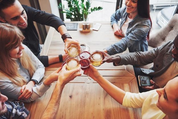 Le persone con bicchieri di whisky o vino festeggiano e brindano
