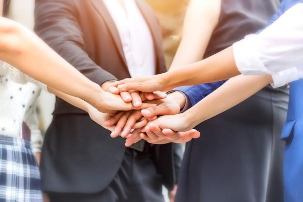 Le persone d'affari stanno unendo le loro mani per mostrare lo spirito sul posto di lavoro.