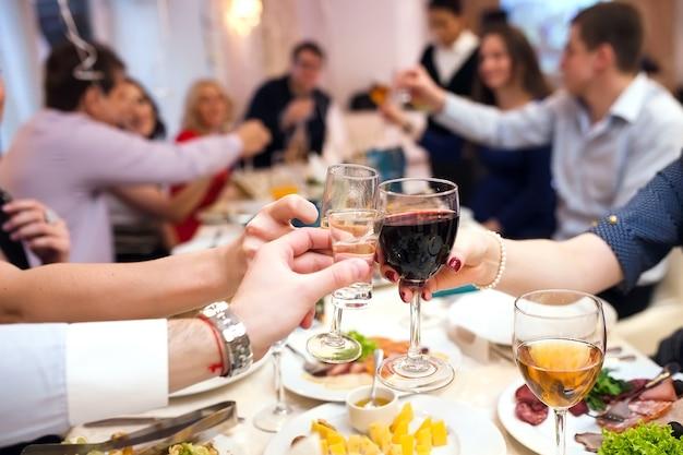 Le persone dell'evento festivo si acclamano a vicenda con champagne.