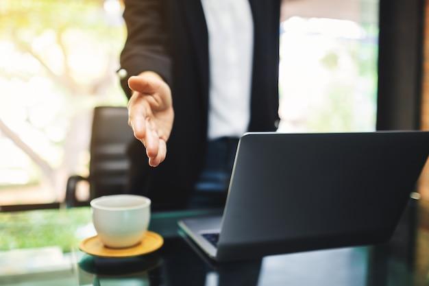 Le persone di affari aprono la mano a stringere le mani con qualcuno in ufficio