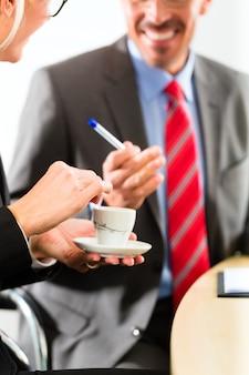 Le persone di affari nell'ufficio di affari bevono il caffè