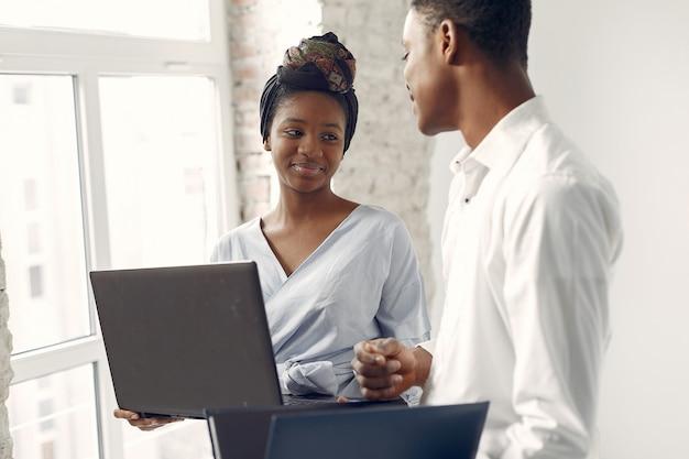 Le persone di colore in piedi su un muro bianco con un computer portatile