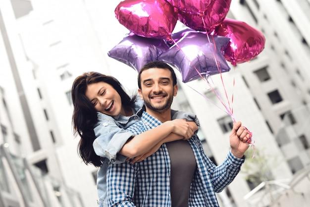 Le persone felici hanno la data in città tenendo palloncini.