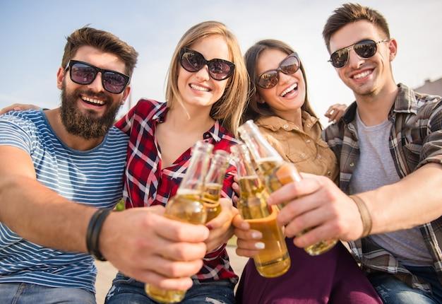 Le persone felici tintinnano gli occhiali sulla natura.