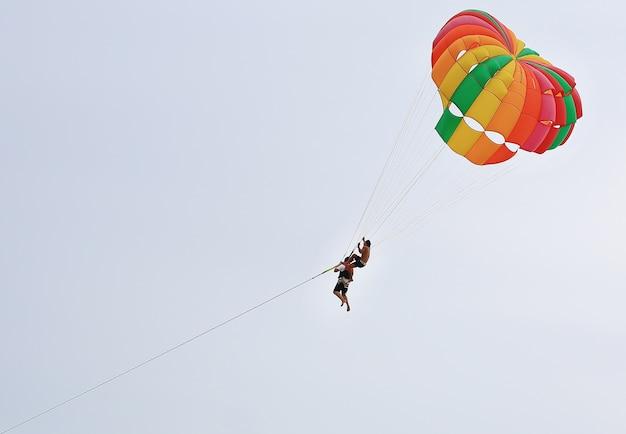 Le persone godono di sport acquatici parasailing