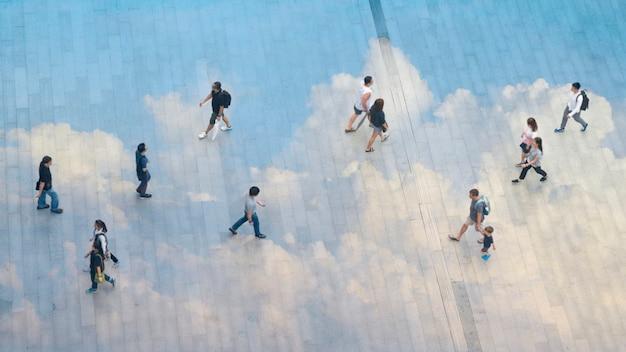Le persone, i gruppi familiari e i bambini camminano attraverso il paesaggio pedonale di cemento con nuvole riflettenti.