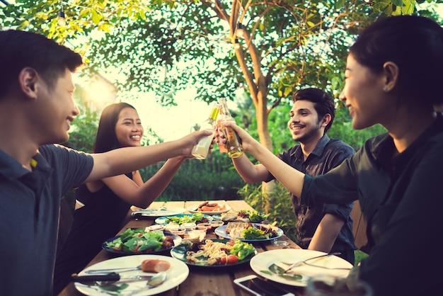 Le persone in asia festeggiano il festival, tintinnano birra e cenano all'aperto