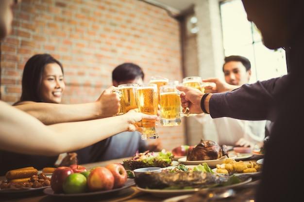 Le persone in asia stanno festeggiando il festival e tintinnano bicchieri di birra e cena felici