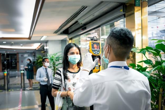Le persone in attesa di controllo della temperatura con thermoscan