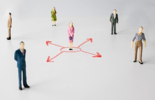 Le persone in miniatura con la freccia rossa rappresentano la distanza sociale del problema con coronavirus o covid-19. concetto di allontanamento sociale.