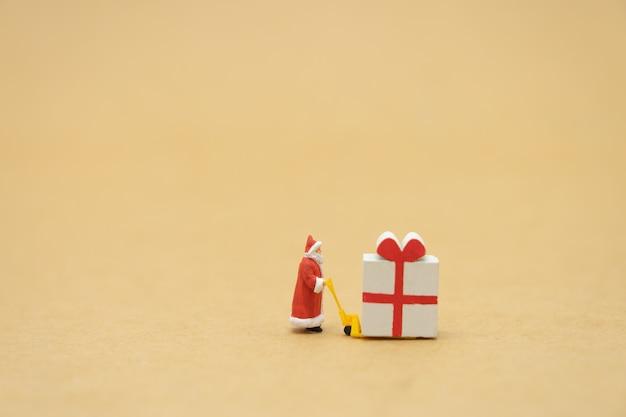 Le persone in miniatura in piedi sull'albero di natale festeggiano il natale il 25 dicembre
