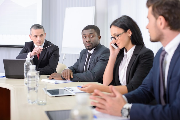 Le persone in ufficio sono sedute al tavolo e discutono.