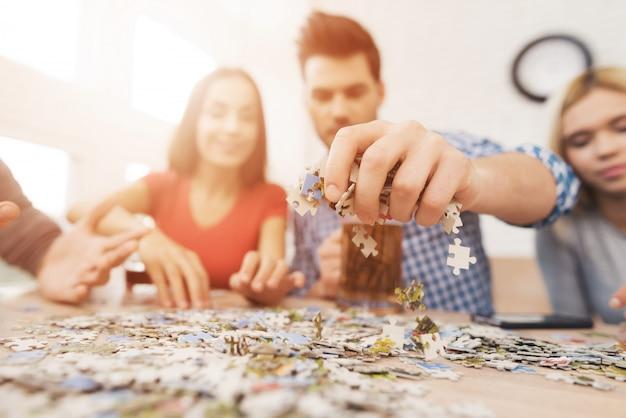 Le persone organizzano puzzle a casa