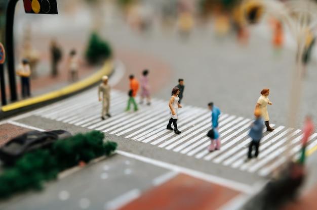 Le persone piccole o piccole camminano su molte strade.
