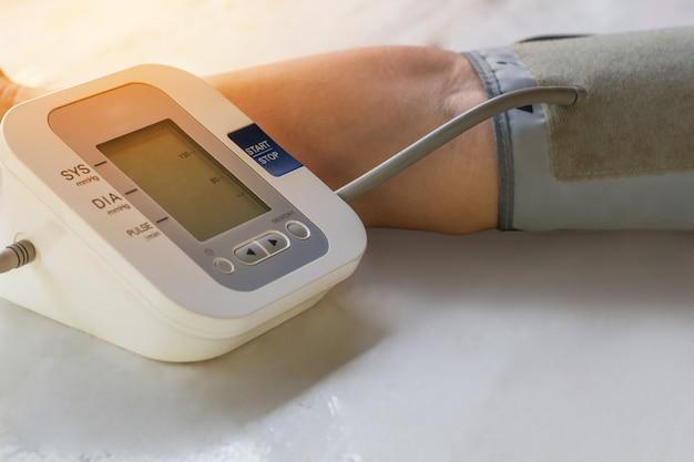 Le persone stanno controllando il monitor della pressione arteriosa e il cardiofrequenzimetro con la pressione digitale.