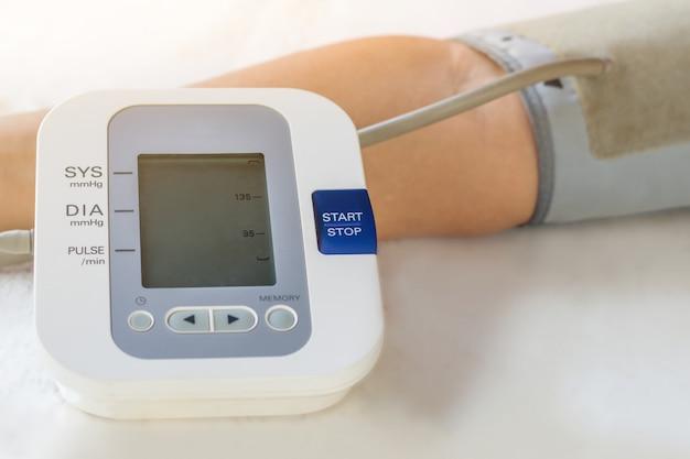 Le persone stanno controllando il monitor della pressione arteriosa e il cardiofrequenzimetro con la pressione digitale