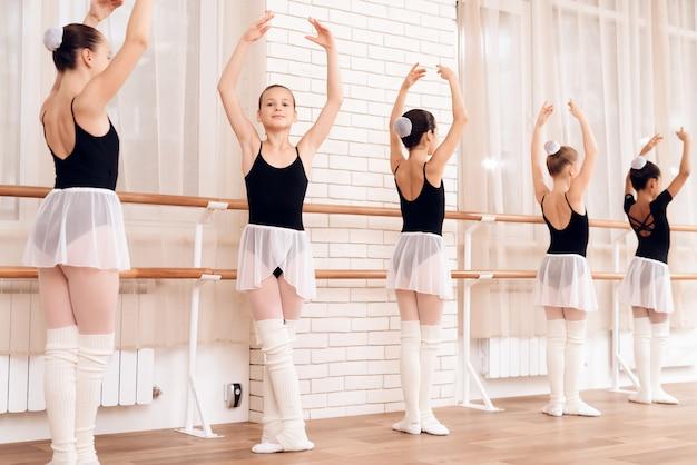 Le persone stanno in posizioni diverse vicino al balletto barr.