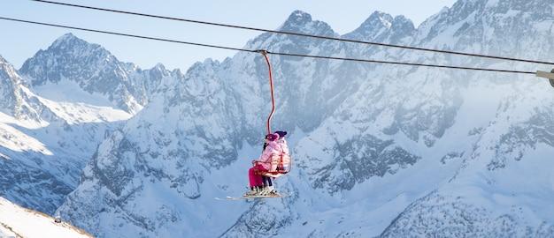 Le persone stanno sollevando su un ascensore aperto in alto nelle montagne del caucaso