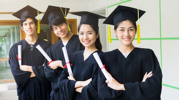 Le persone studenti uomo e donna con abiti da laurea neri tengono il diploma