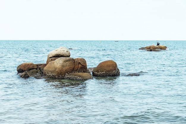 Le pietre del mare in mezzo al mare con il cielo luminoso sullo sfondo in chon buri, tailandia.