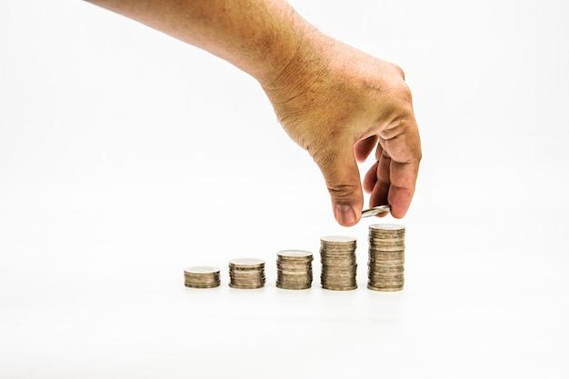 Le pile della moneta con la mano su fondo bianco