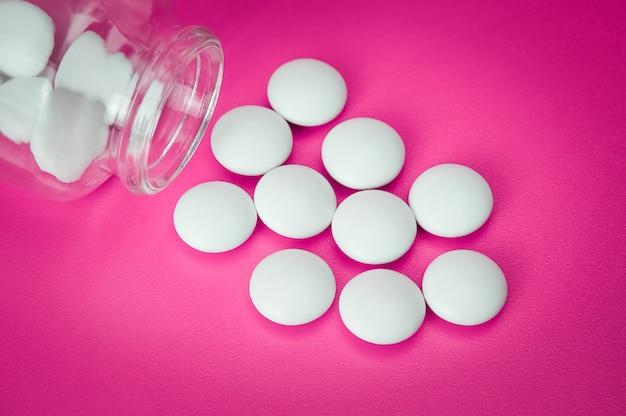 Le pillole bianche sono sparse da una bottiglia di vetro. la vignettatura