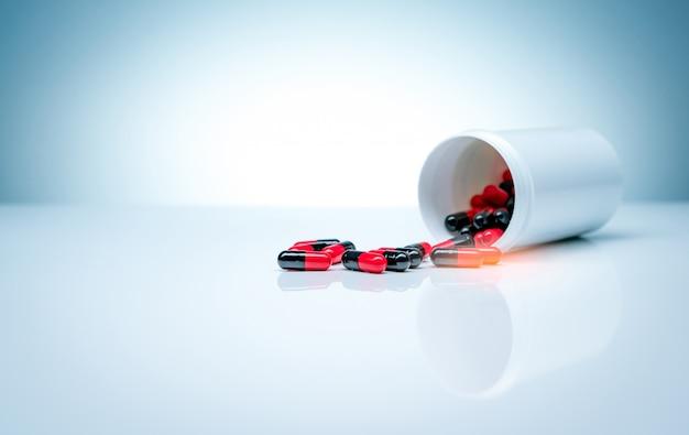 Le pillole della capsula antibiotica rosso-nere si sono sparse dalla bottiglia di plastica della droga su fondo bianco. industria farmaceutica. concetto di resistenza ai farmaci antibiotici.
