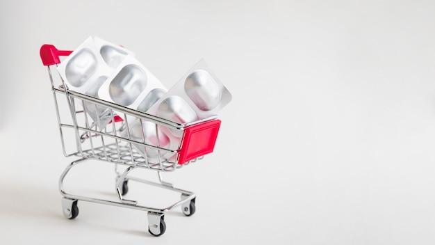 Le pillole della medicina imballano in carrello miniatura su fondo bianco