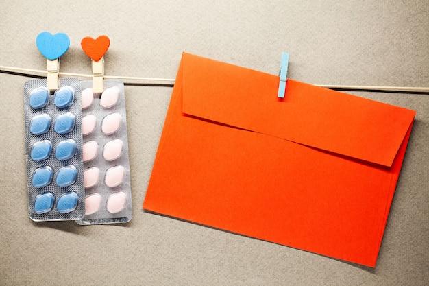 Le pillole e la busta maschii di salute appendono su una corda