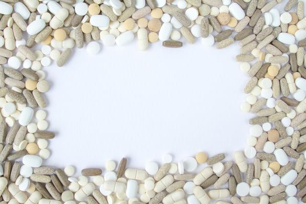 Le pillole mediche variopinte si liberano su un fondo bianco