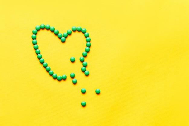 Le pillole rotonde verdi delle pillole brocken il cuore modellano su fondo yuellow