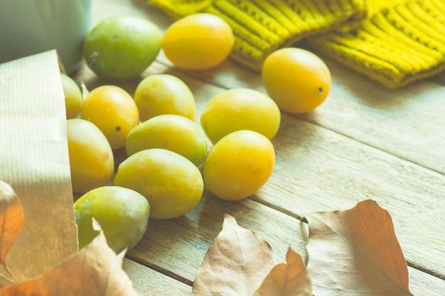 Le prugne trasparenti gialle mature in sacco di carta del mestiere di brown hanno sparso